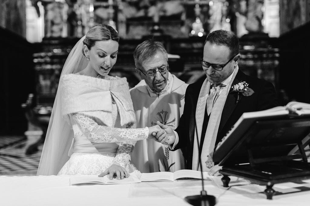 Riccardo e Irene sono uniti mano nella mano mentre il prete legge i doveri degli sposi