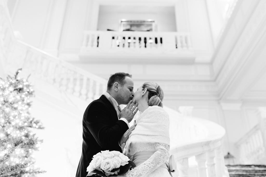 I due sposi si baciano all'interno del candido Palazzo Parigi