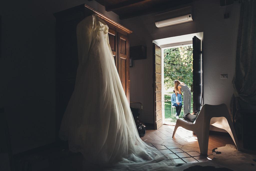Il vestito della sposa Silvia è illuminato da una morbida luce dalla porta