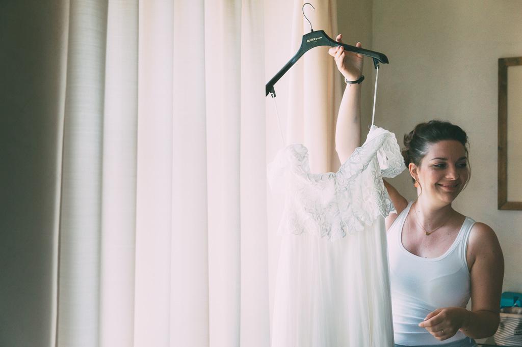 La sposa sostiene orgogliosa il suo abito