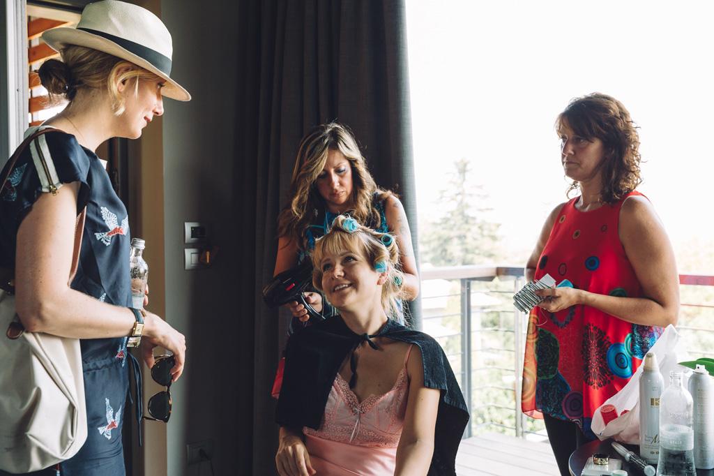 Le damigelle acconciano i capelli della sposa