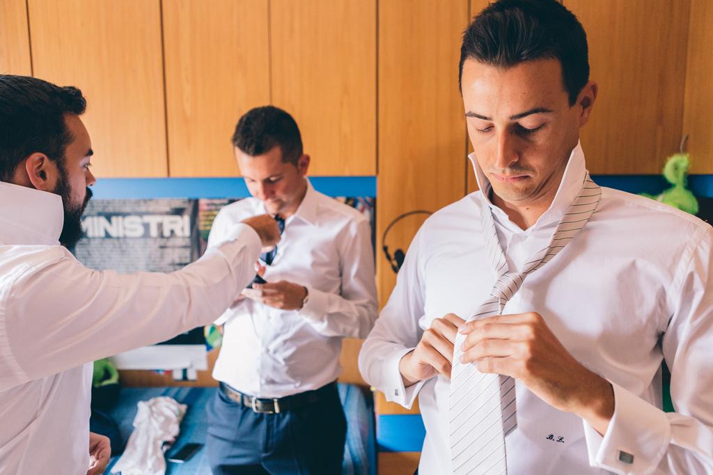 Lo sposo indossa la cravatta in preparazione della cerimonia di matrimonio