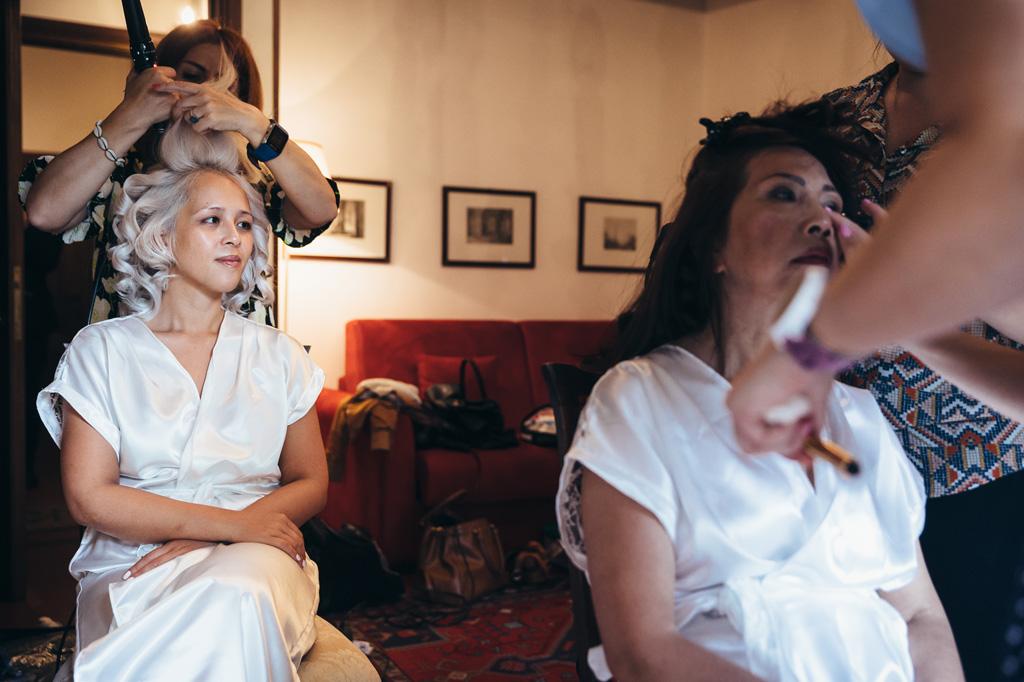 La sposa è acconciata dalla parrucchiera durante la preparazione