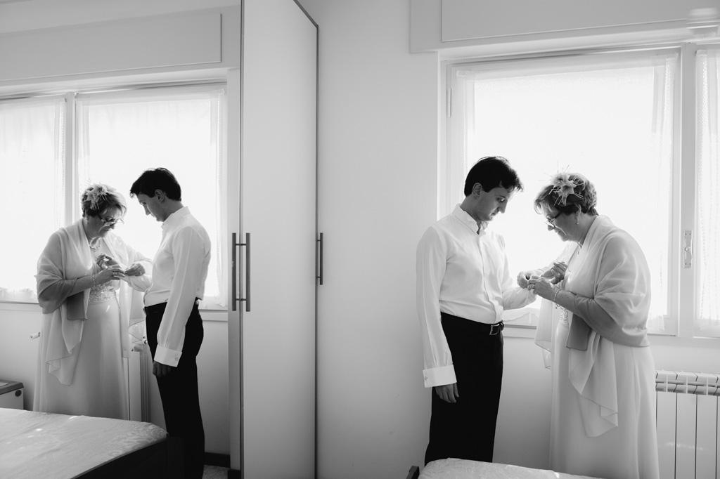 La madre acconcia lo sposo in preparazione della cerimonia