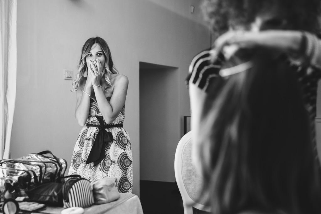 Una damigella in un'espressione basita osserva la splendida acconciatura della sposa in uno scatto del fotografo Alessandro Della Savia
