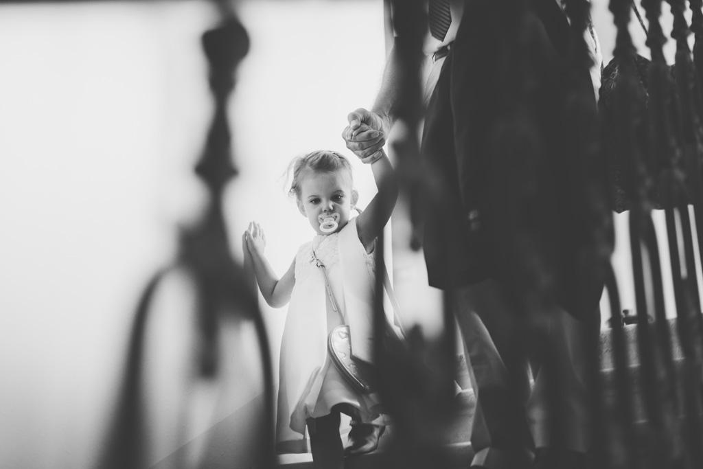 Una bambina scende le scale accompagnata da una damigella