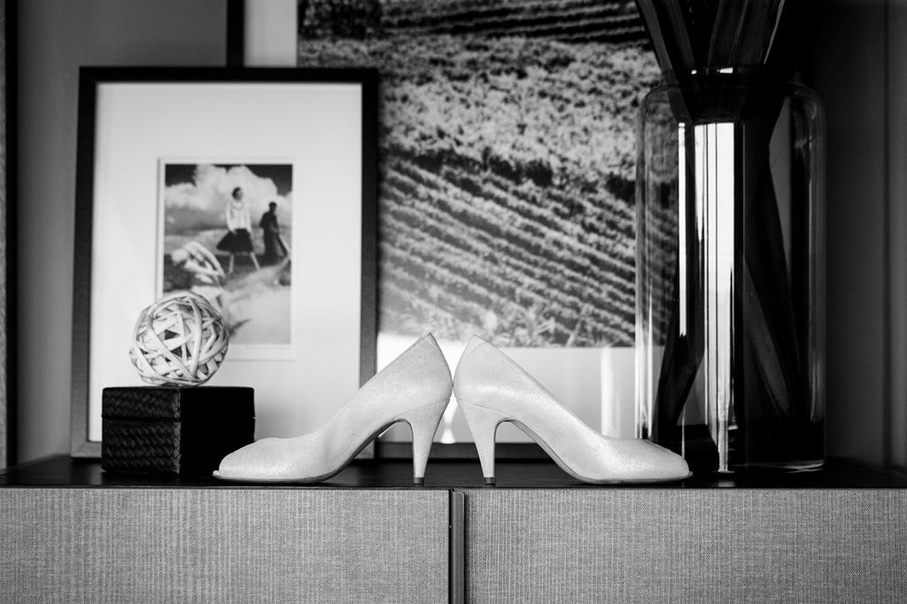 L'eleganza delle scarpe della sposa riprese davanti a delle fotografie incorniciate