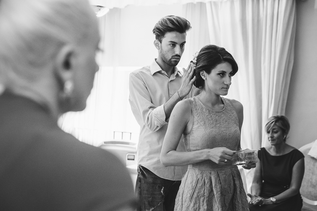 Il parrucchiere perfeziona gli ultimi dettagli dei capelli della sposa