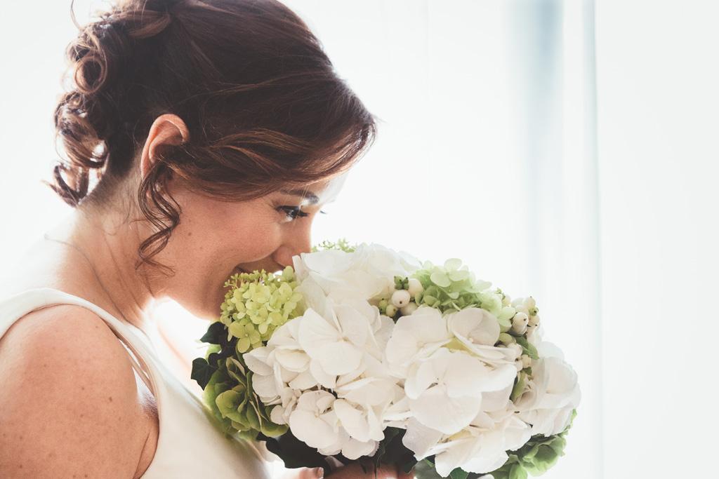 la sposa aspira il profumo del bouquet