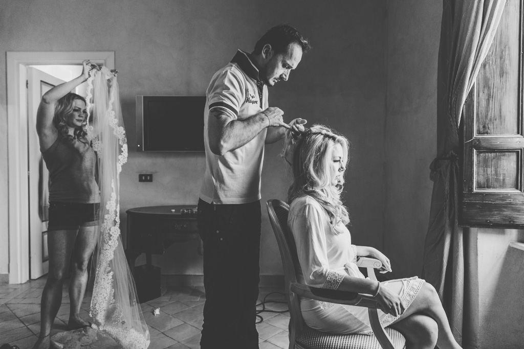 Il parrucchiere sistema i capelli di Brittney durante la preparazione