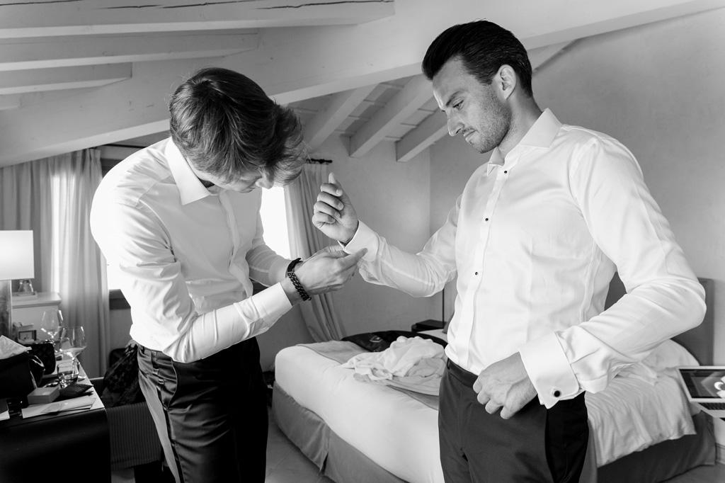 Un testimone aiuta lo sposo a indossare i bottoni della camicia