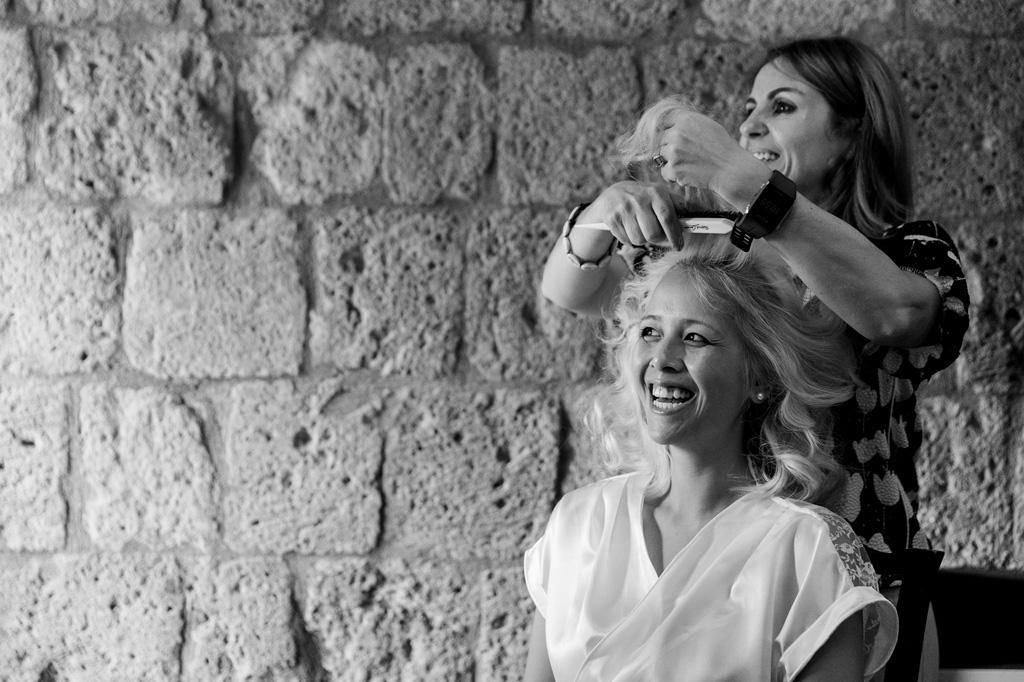 La parrucchiera acconcia la sposa in vista delle nozze di matrimonio