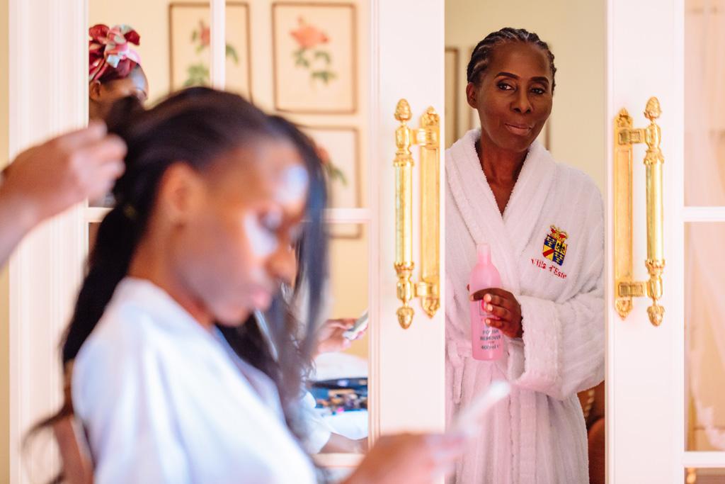 La parrucchiera sistema la sposa sotto lo sguardo attento della madre