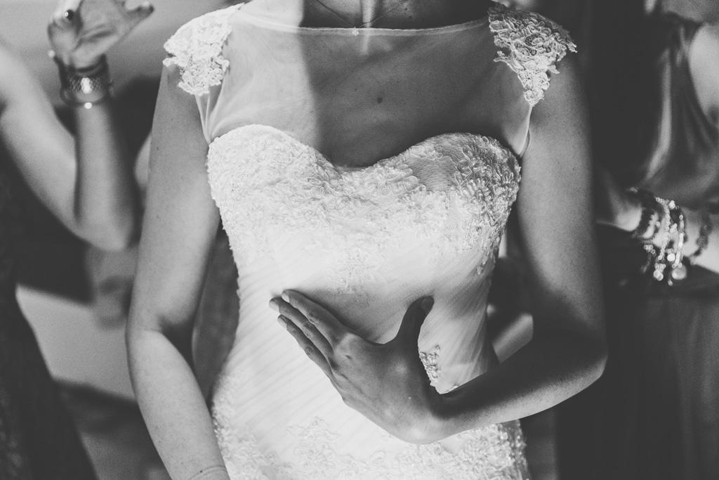 Un particolare del vestito della sposa durante la preparazione