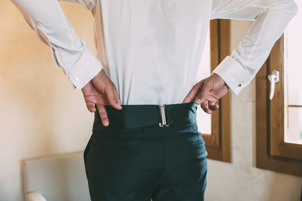 Lo sposo aggiusta i pantaloni in preparazione della cerimonia