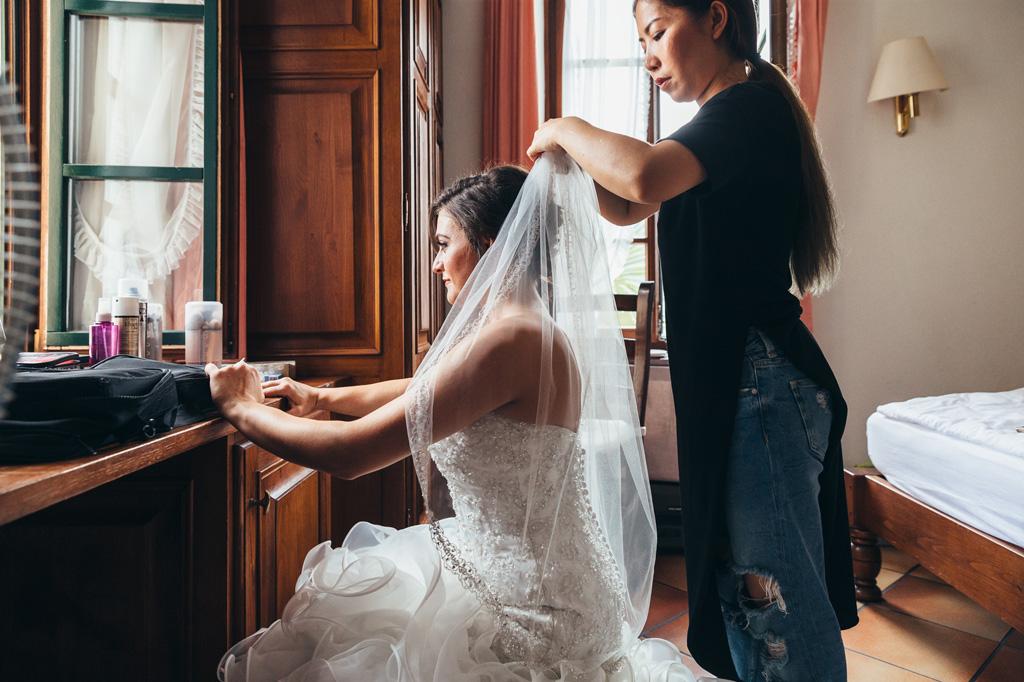 La truccatrice sistema gli ultimi dettagli del vestito della sposa Loreanne