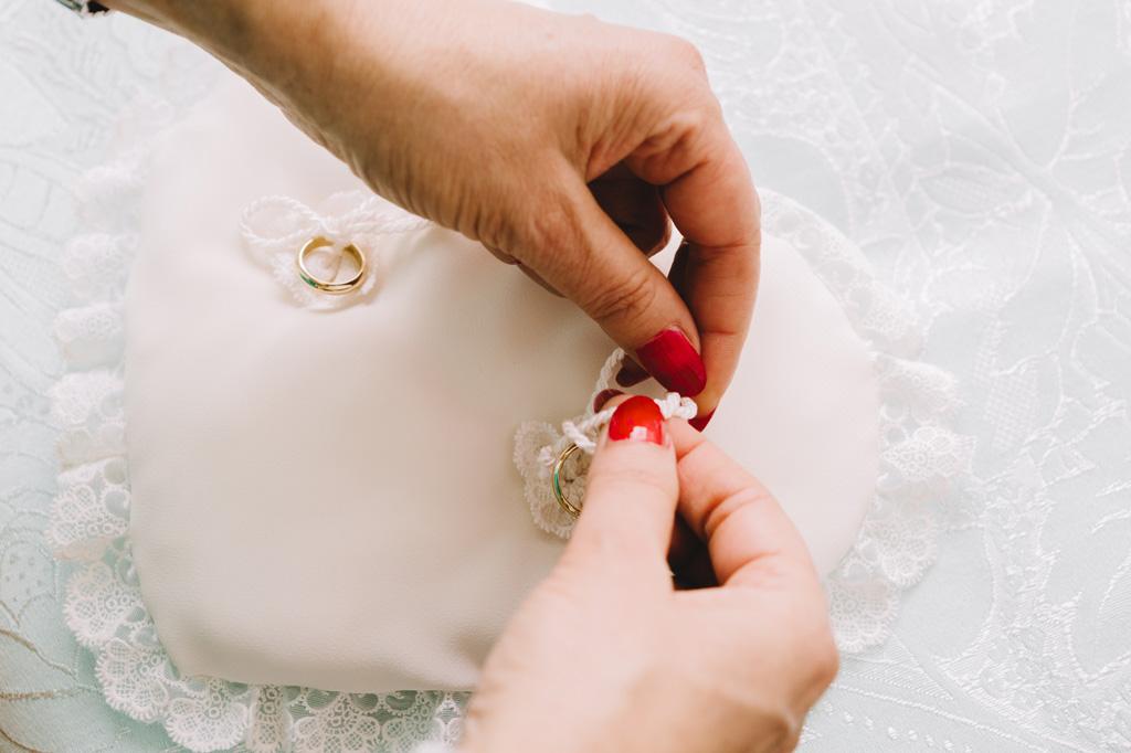 Le fedi nunziali accuratamente rilegate su un candido cuscinetto