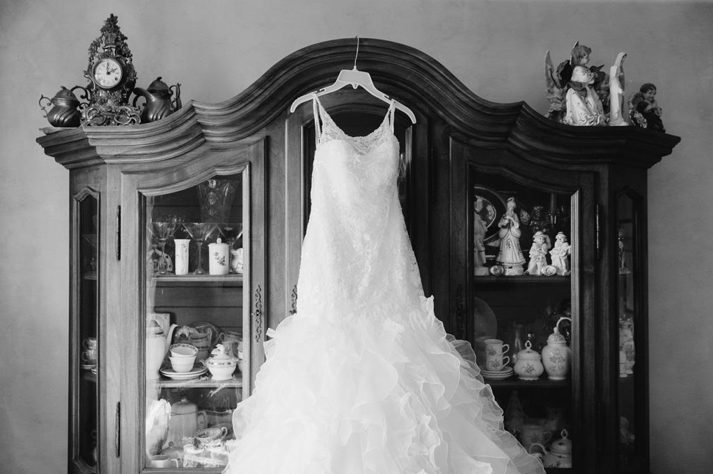 L'abito della sposa Giorgia appeso su un armadio antiquato con all'interno oggetti di porcellana
