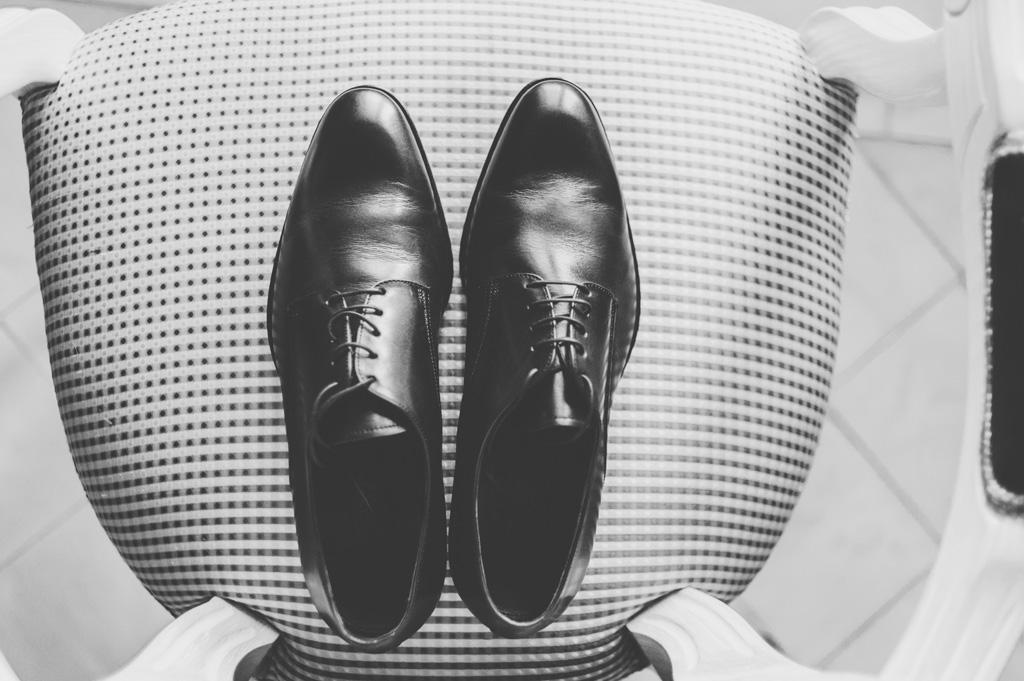 Le scarpe dello sposo sono posate sopra una sedia