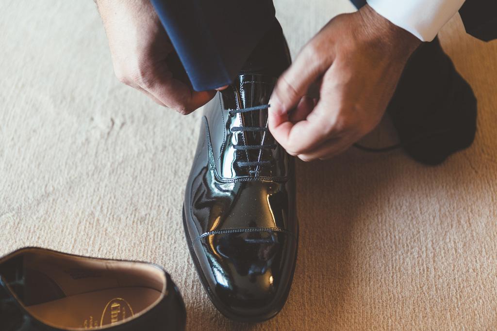 Lo sposo Luca indossa le scarpe da cerimonia