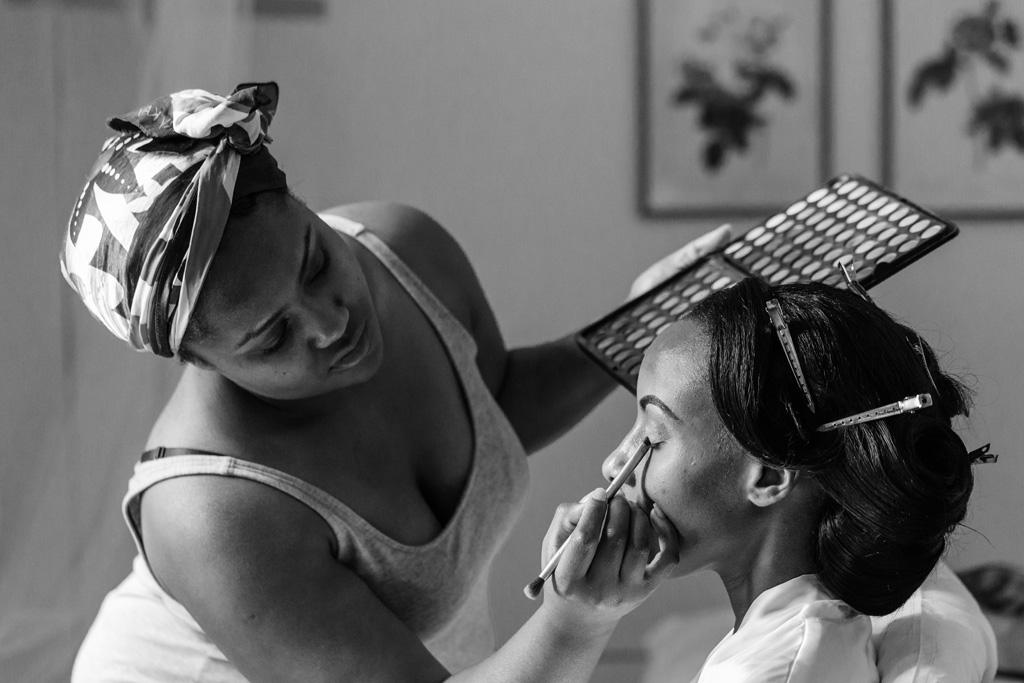 Una damigella decora il viso della sposa
