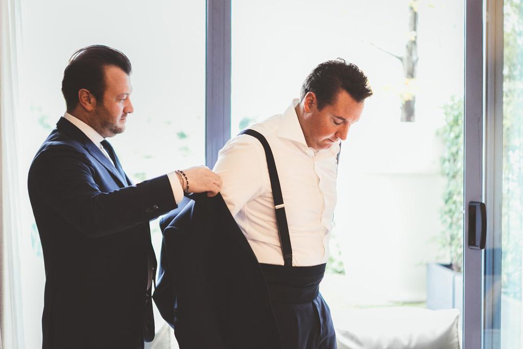 Un testimone aiuta lo sposo Luca a indossare una giacca