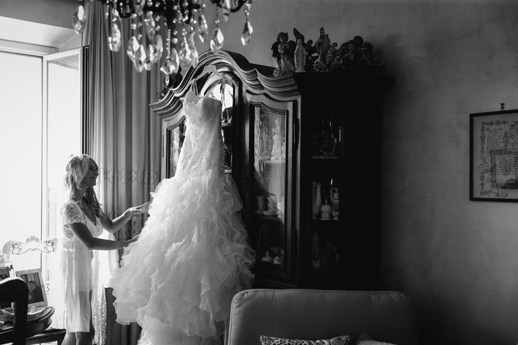 La sposa accarezza il suo abito che indosserà alla cerimonia di matrimonio