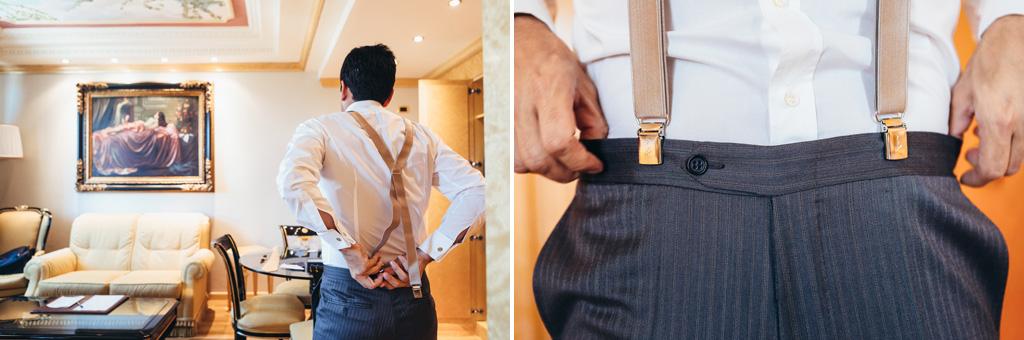 LO sposo aggiusta i pantaloni e le bretelle durante la preparazione