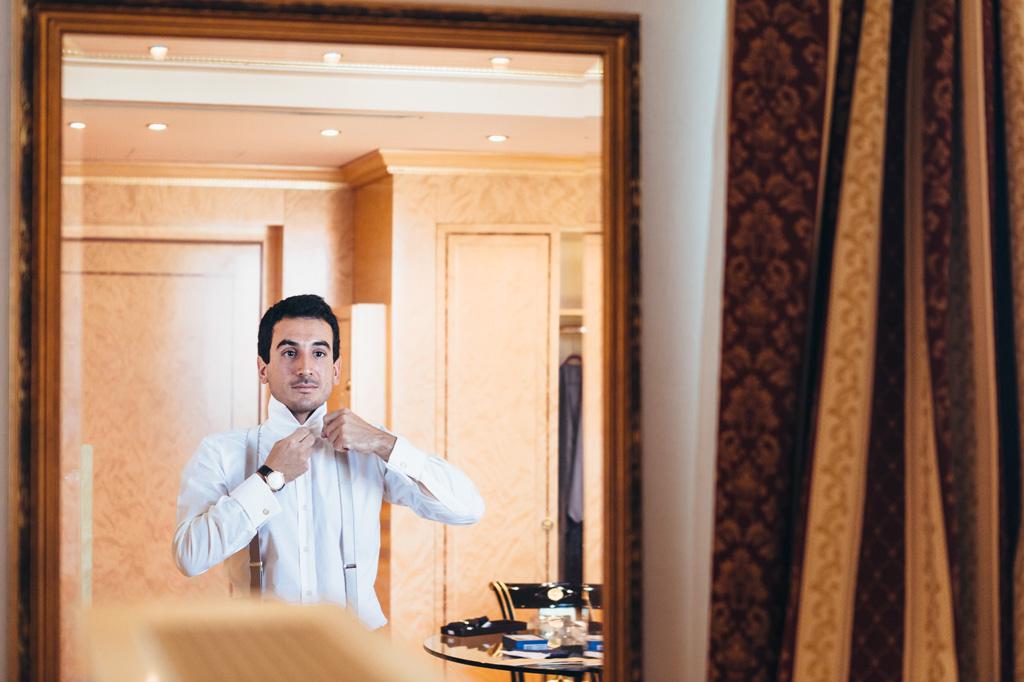 Lo sposo indossa una camicia bianca davanti allo specchio