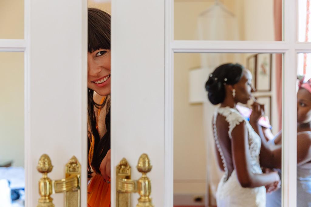 Una damigella scruta dalla fessura della porta la preparazione della sposa