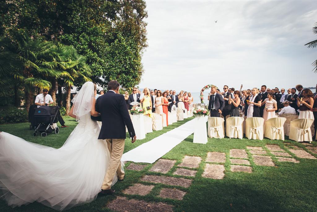 Il padre accompagna la sposa per celebrare le nozze di matrimonio presso il cortile di Torre San Marco