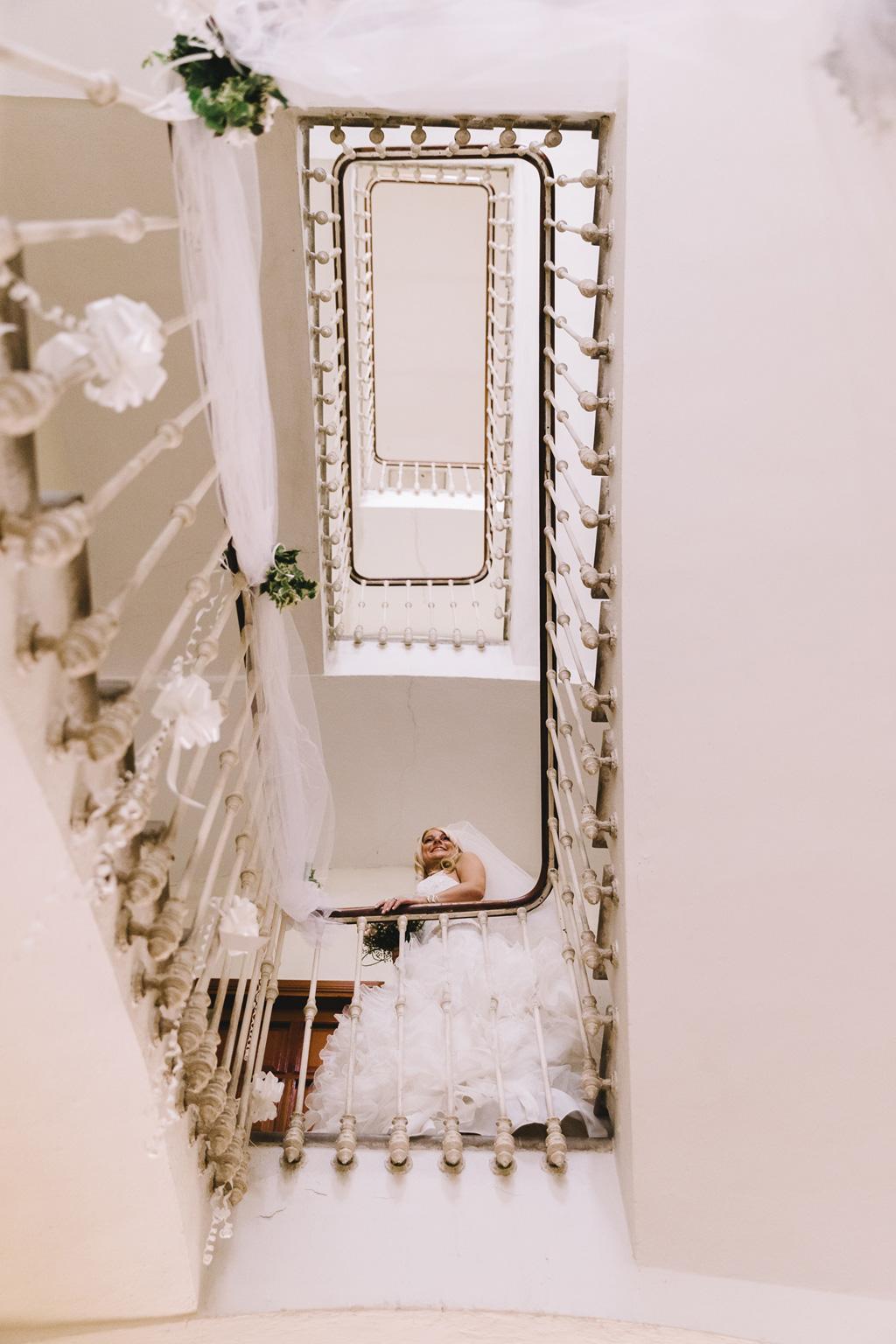 La sposa scende le scale con un sorriso raggiante
