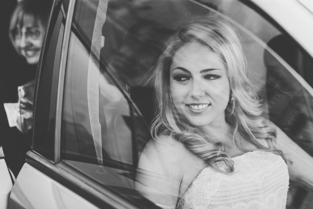 La sposa sorride raggiante dalla macchina con lo sguardo in direzione della Basilica