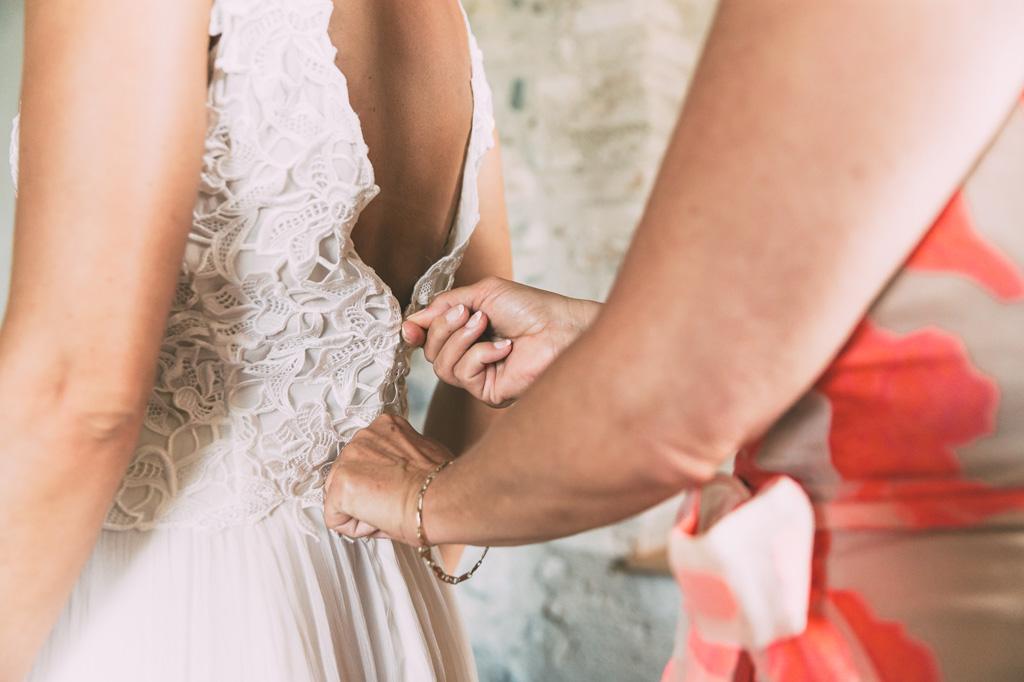 La madre della sposa sistema il vestito della sposa