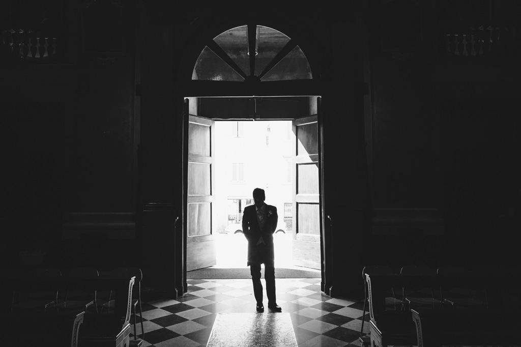 Il primo invitato alla cerimonia attende paziente nella chiesa a Bergamo