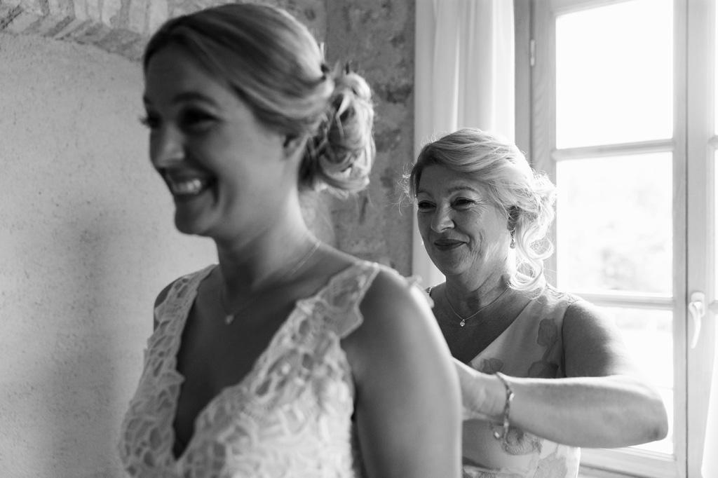 La madre della sposa sistema con cura il vestito della figlia Emily