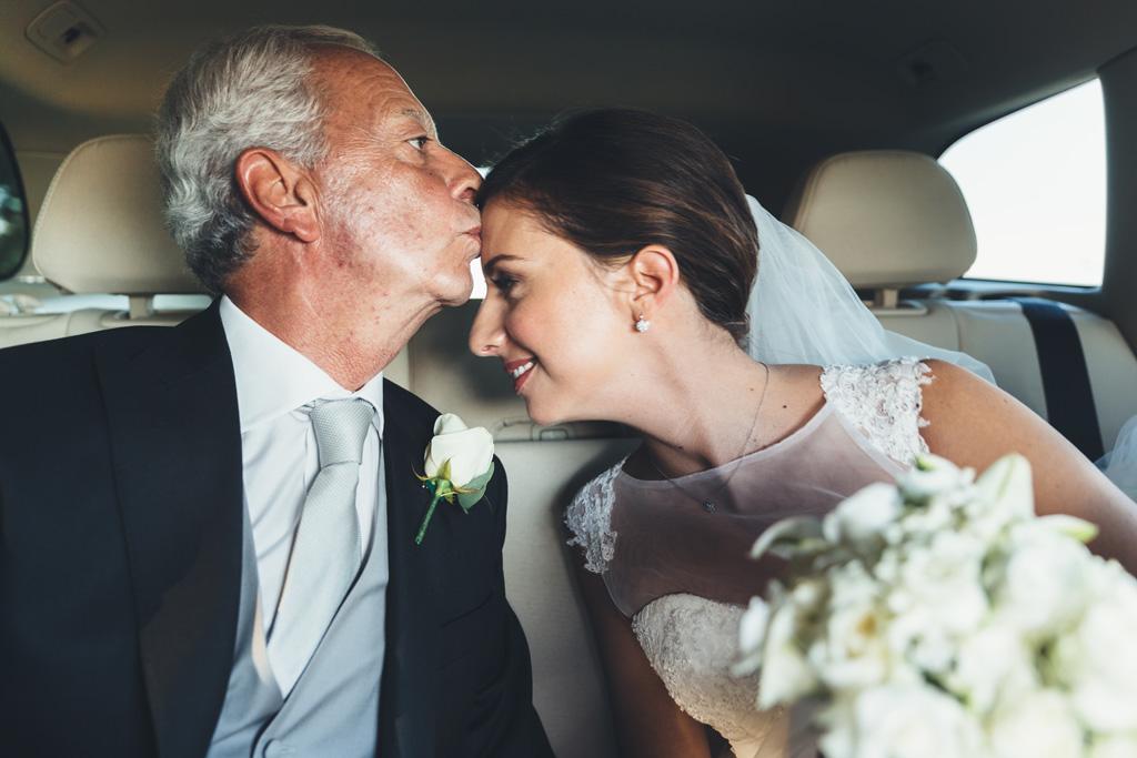 Il padre bacia la fronte delle sposa in macchina
