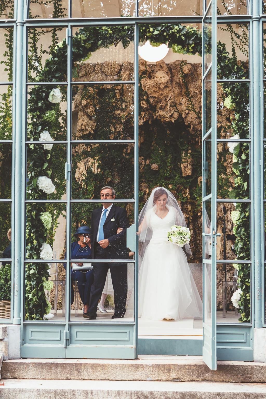 Il padre e la figlia Daniela superano la porta a vetro per raggiungere lo sposo in una foto di Della Savia fotografo presso Milano