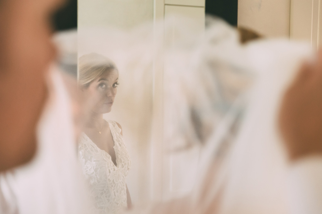 La sposa si specchia davanti allo specchio in un gioco di riflessi scattato da Alessandro Della Savia