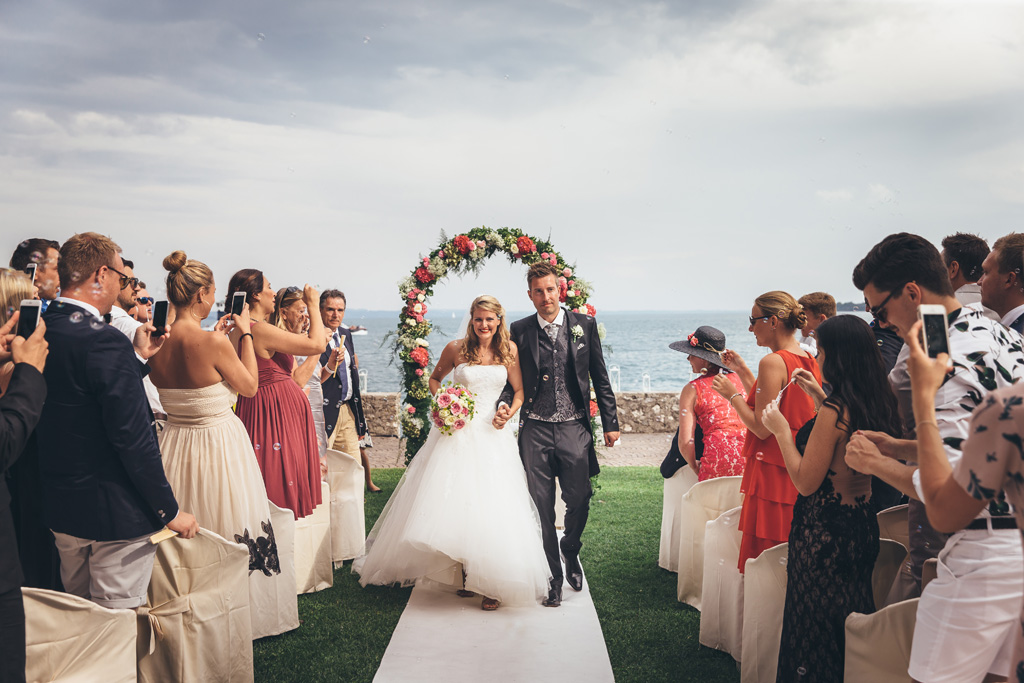 I due sposi attraversano telo bianco a seguito della cerimonia di matrimonio