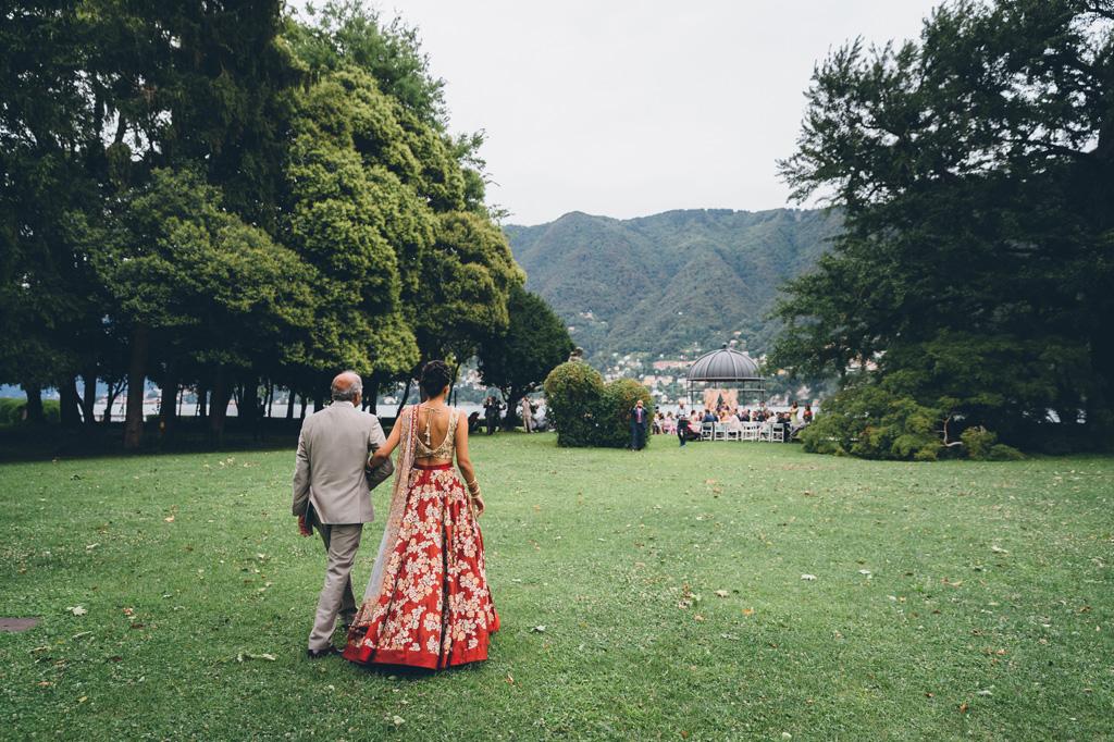 Il padre cammina a braccetto con la sposa in direzione del luogo della cerimonia