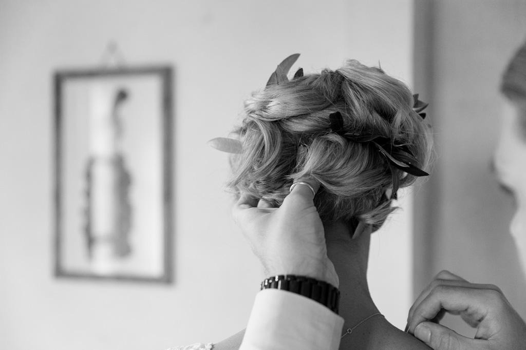 Il parrucchiere sistema i capelli della sposa