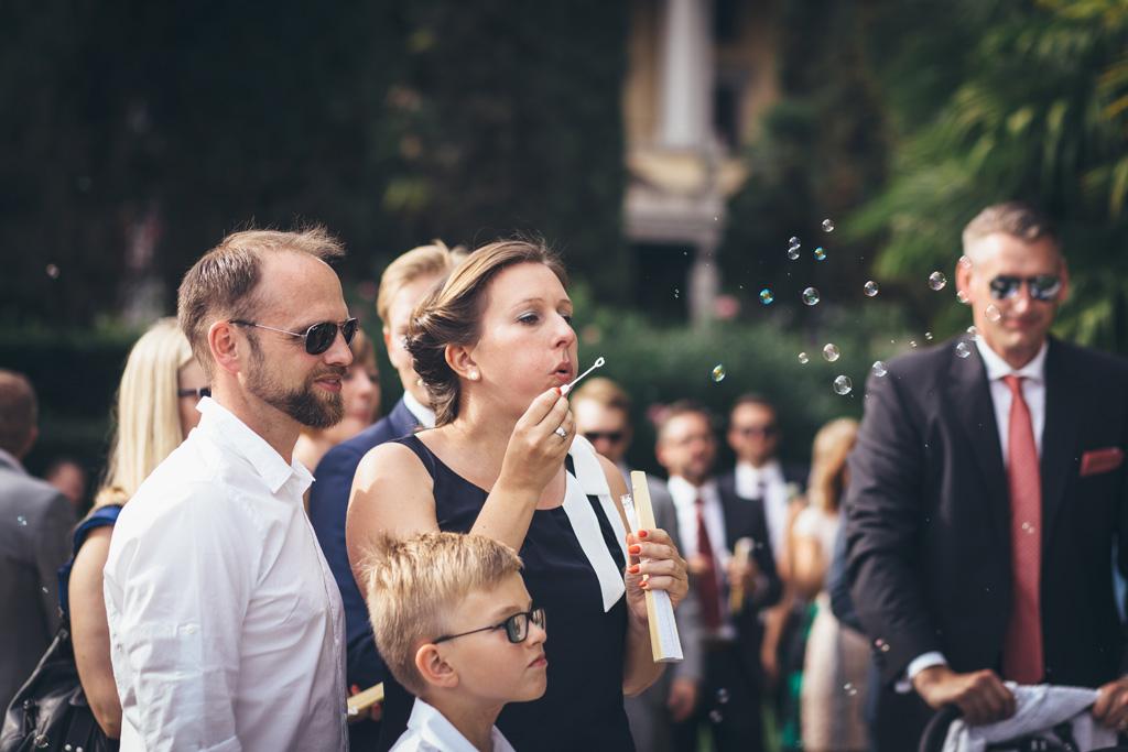 Un'invitata soffia le bolle di sapone in direzione degli sposi