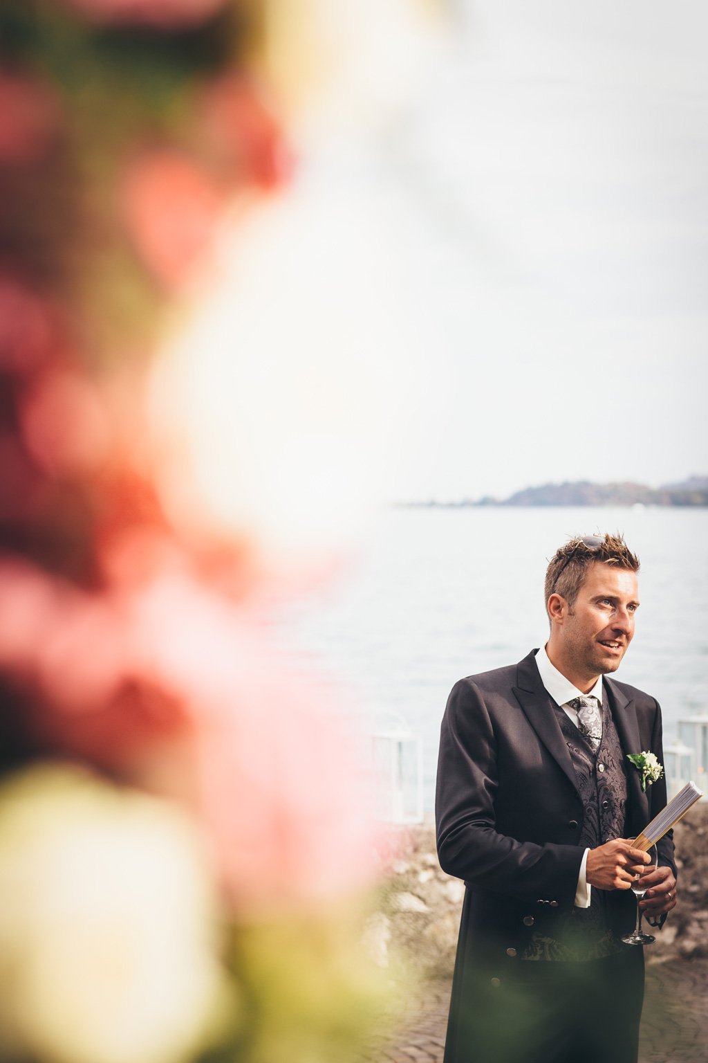 Lo sposo tiene un bicchiere e un ventaglio in mano