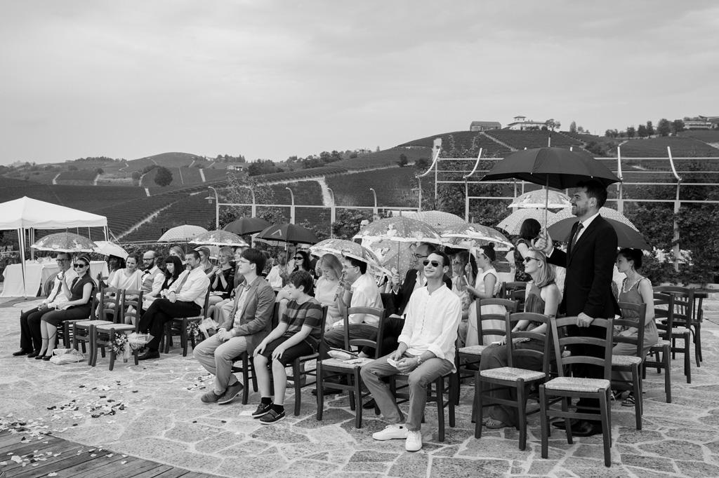 Gli invitati assistono al matrimonio sotto gli ombrelli
