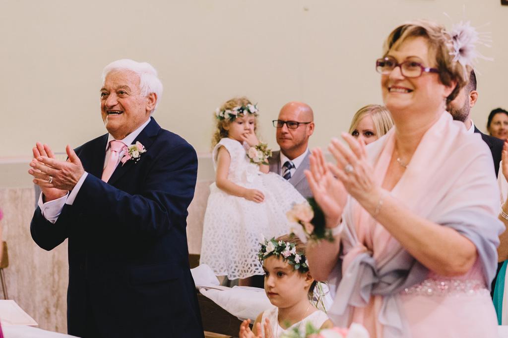Gli ospiti applaudono fragorosamente gli sposi durante la cerimonia di matrimonio