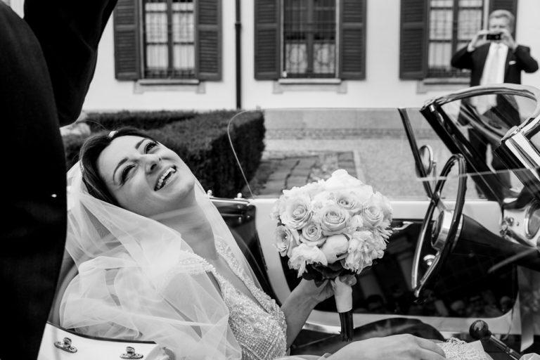 La sposa sorride raggiante in macchina