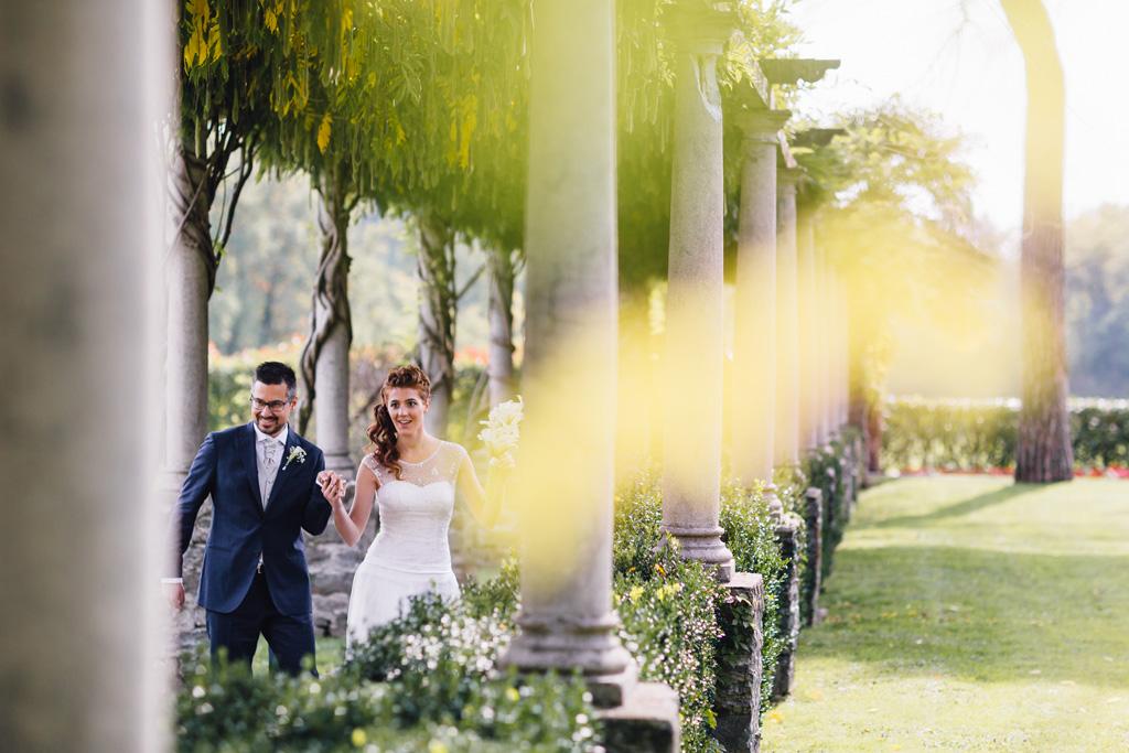 I due sposi passeggiano mano nella mano tra le colonne della location di Villa Martinelli