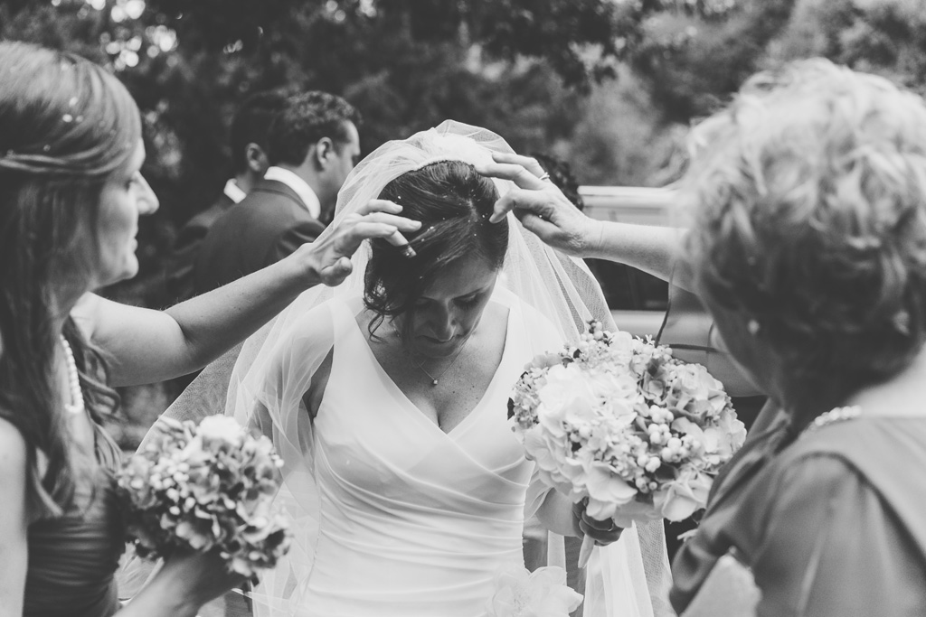 Alcuni parenti sistemano i capelli della sposa ricoperti di riso