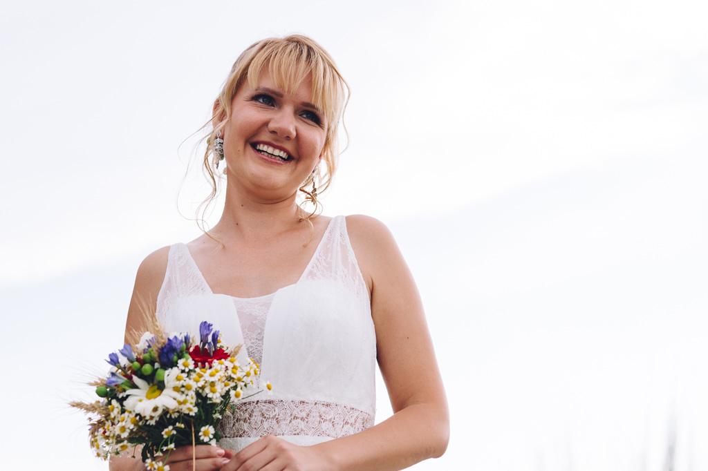 La sposa sorride con il bouquet in mano ritratta da Alessandro Della Savia